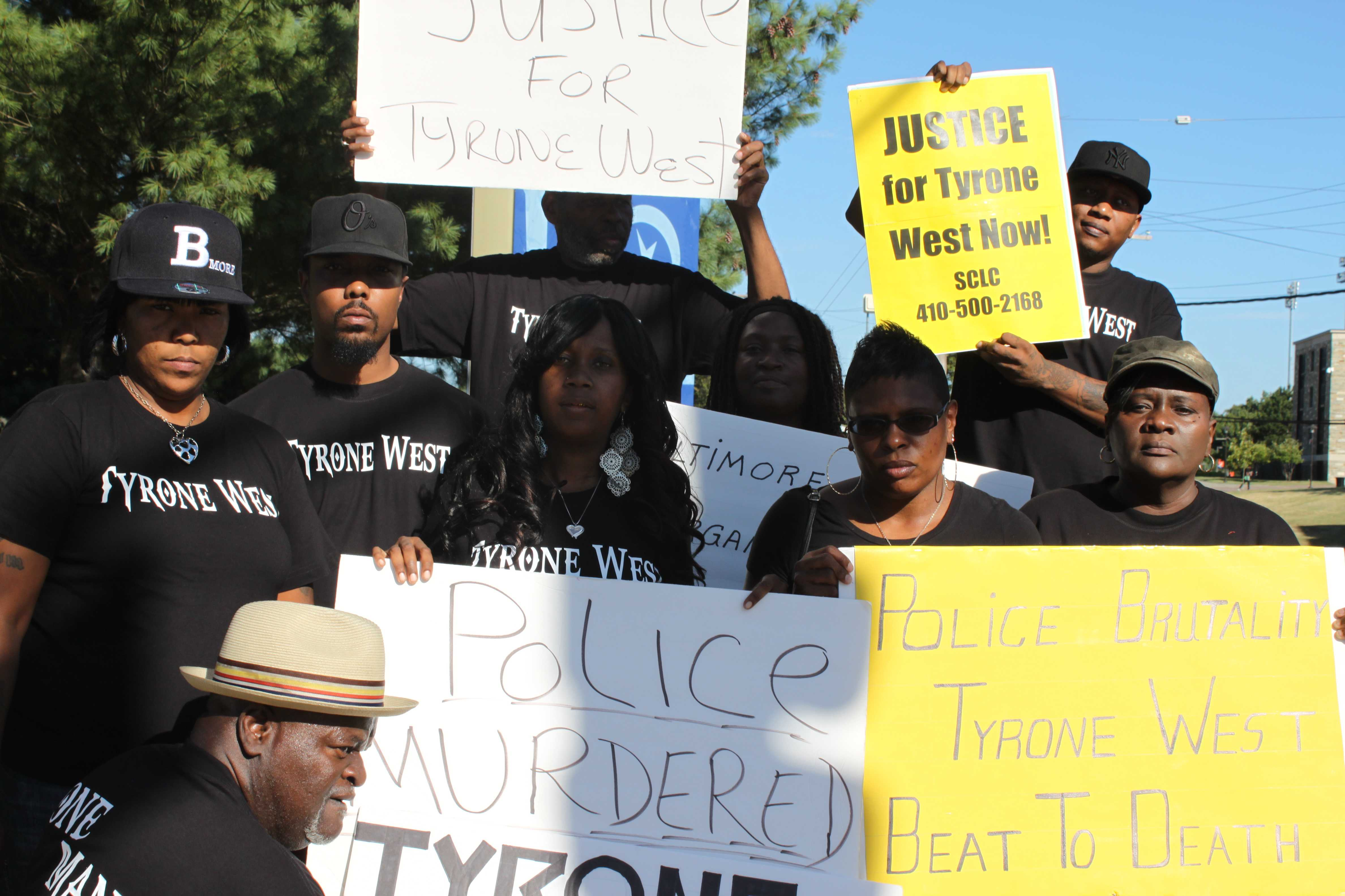 Family and friends of Tyrone West hold their protest signs.