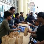 Volunteers distributing food and beverages.