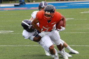 Senior receiver Thomas Martin fights for extra yards after a reception against Holy Cross. Photo by Terry Wright.