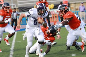 Holy Cross quarterback Peter Pujals scrambles for extra yardage. Photo by Terry Wright.