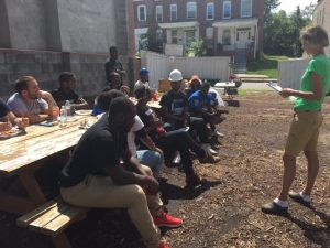 Volunteers from Morgan State University and Johns Hopkins University take a lunch break and learn about Habitat for Humanity. Photo by Jazmine Hawes.