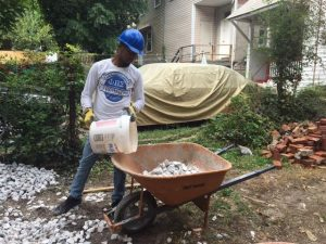 Senior Ricco Peña fills a wheelbarrow with rocks while volunteering with Habitat for Humanity. Photo by Jazmine Hawes.